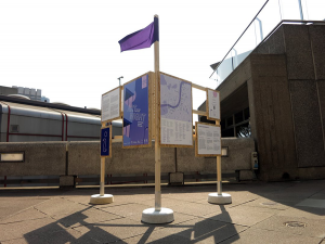 A large wooden Structure with a purple flag on top displays information and a map for Art Night 2018.