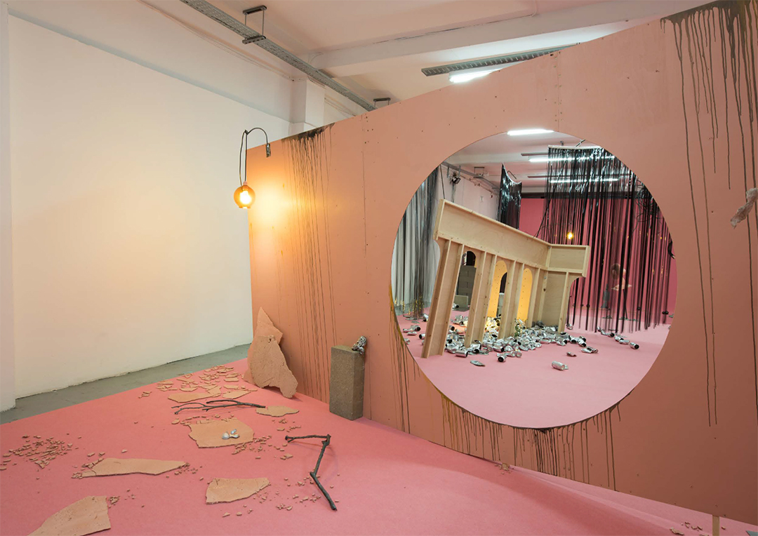 A large crcular mirror reflects what resembles greek ruins in a pink room
