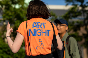 A girl in a bright Orange ART Night Guides BSL T-shirt signs with a man