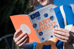 A girl reads an orange and blue Visitor Guide form Art night 2017