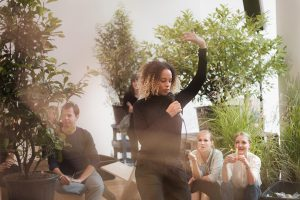 The artist dressed in black dances with a microphone in a room full of greenery while members of audience looks on