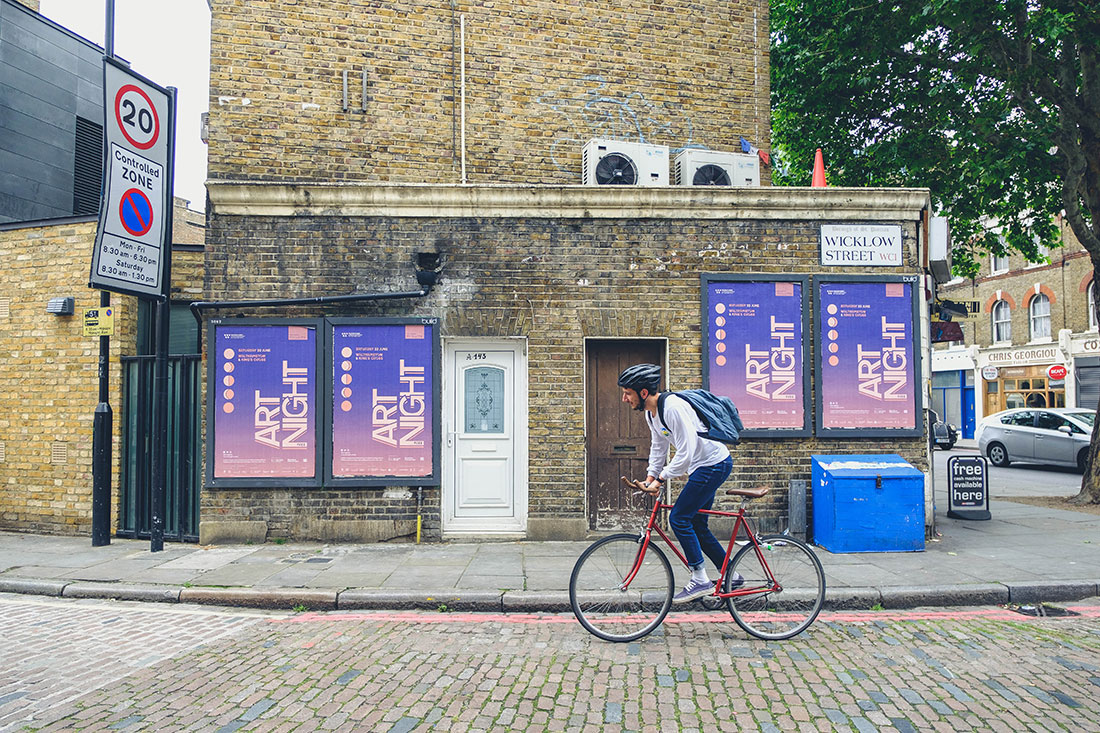 A man cycles by a series of ART Night 2019 Posters on a cobbled street