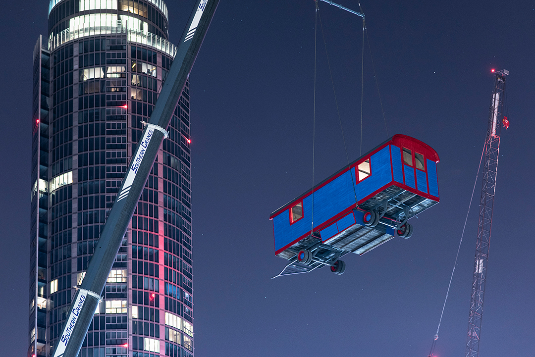 A blue caravan is suspended high in the air with a skyscraper in the background