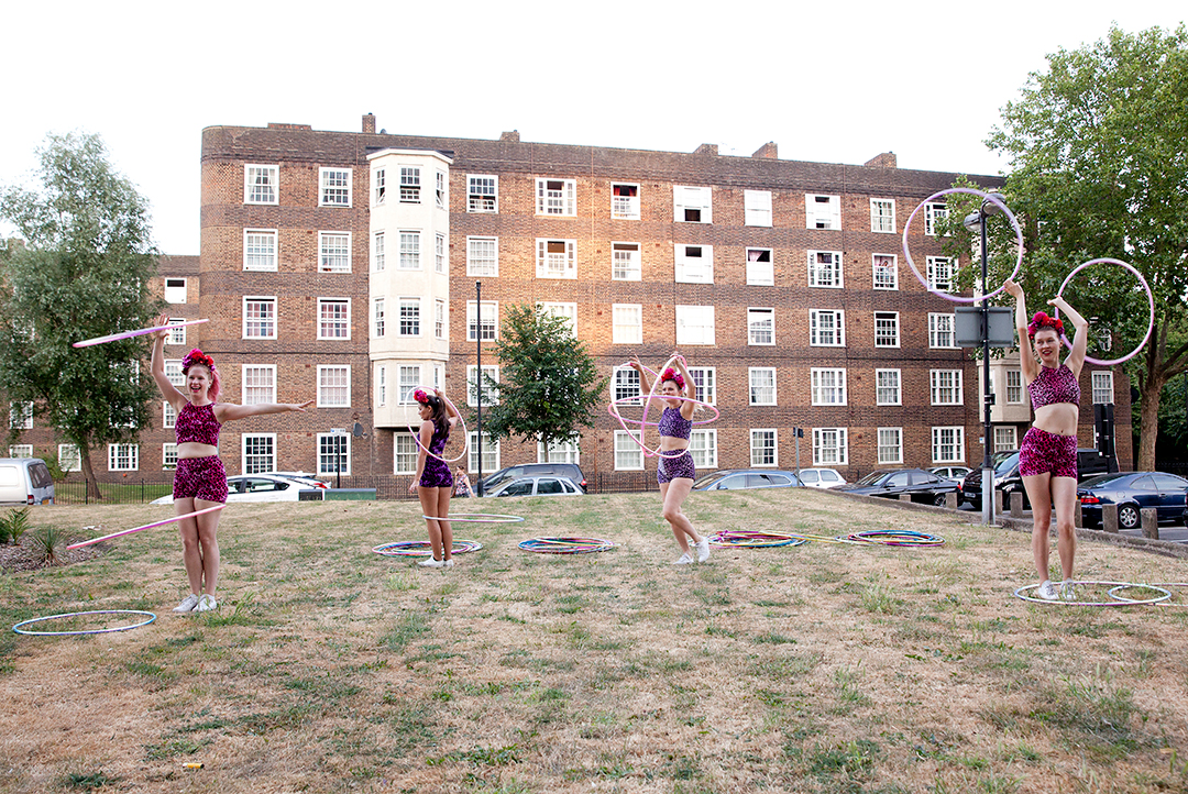 4 women dance wit hula hoops on a housing estate in South London