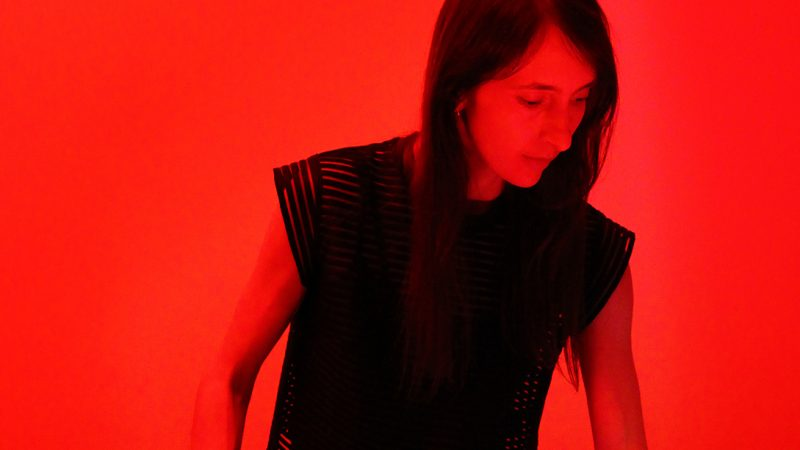 A woman with long dark hair is bathed in red light