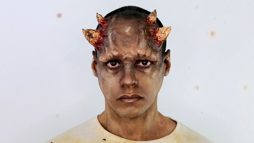 A person wears facial make-up which resembles a protruding brow and horns