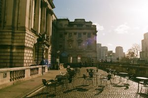 A sunny view of the cobbled river terrace outside Somerset House with tables and chairs