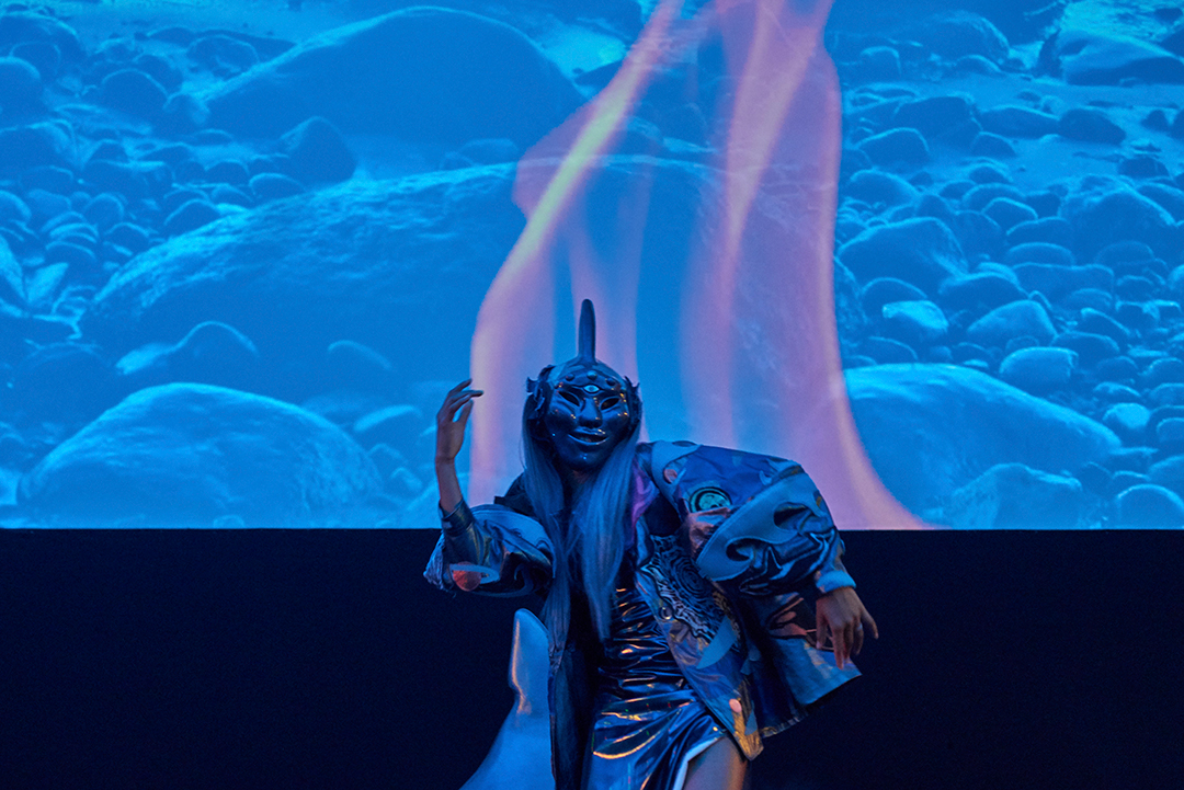 A dancer in a mask dances in front of a blue projection as part of Art Night 2019